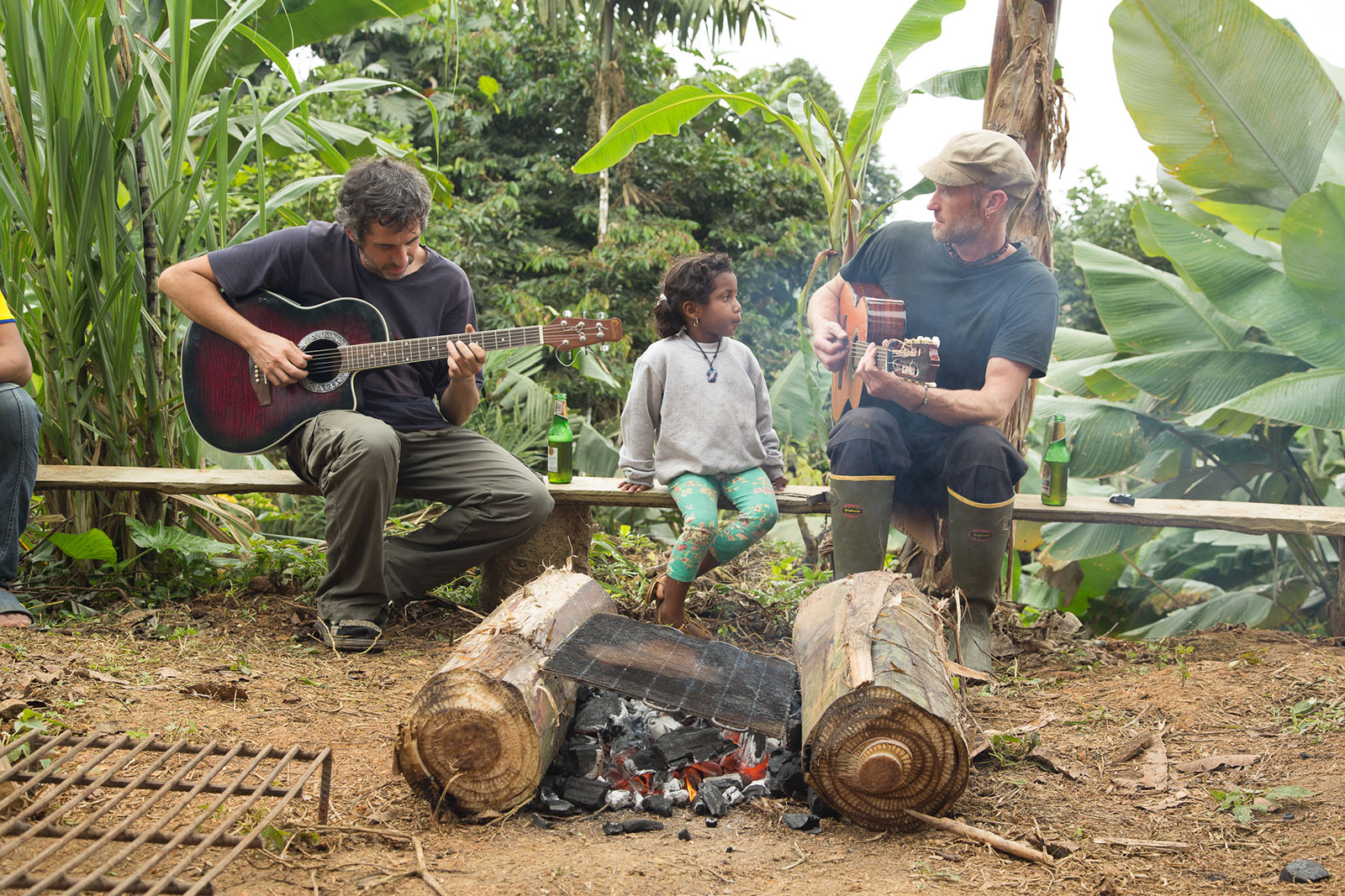 Team members play guitar for visitors while sitting around a fire