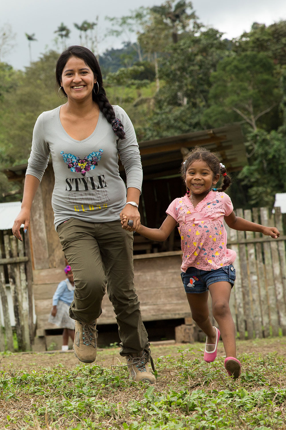 A woman and a young girl hold hands while running