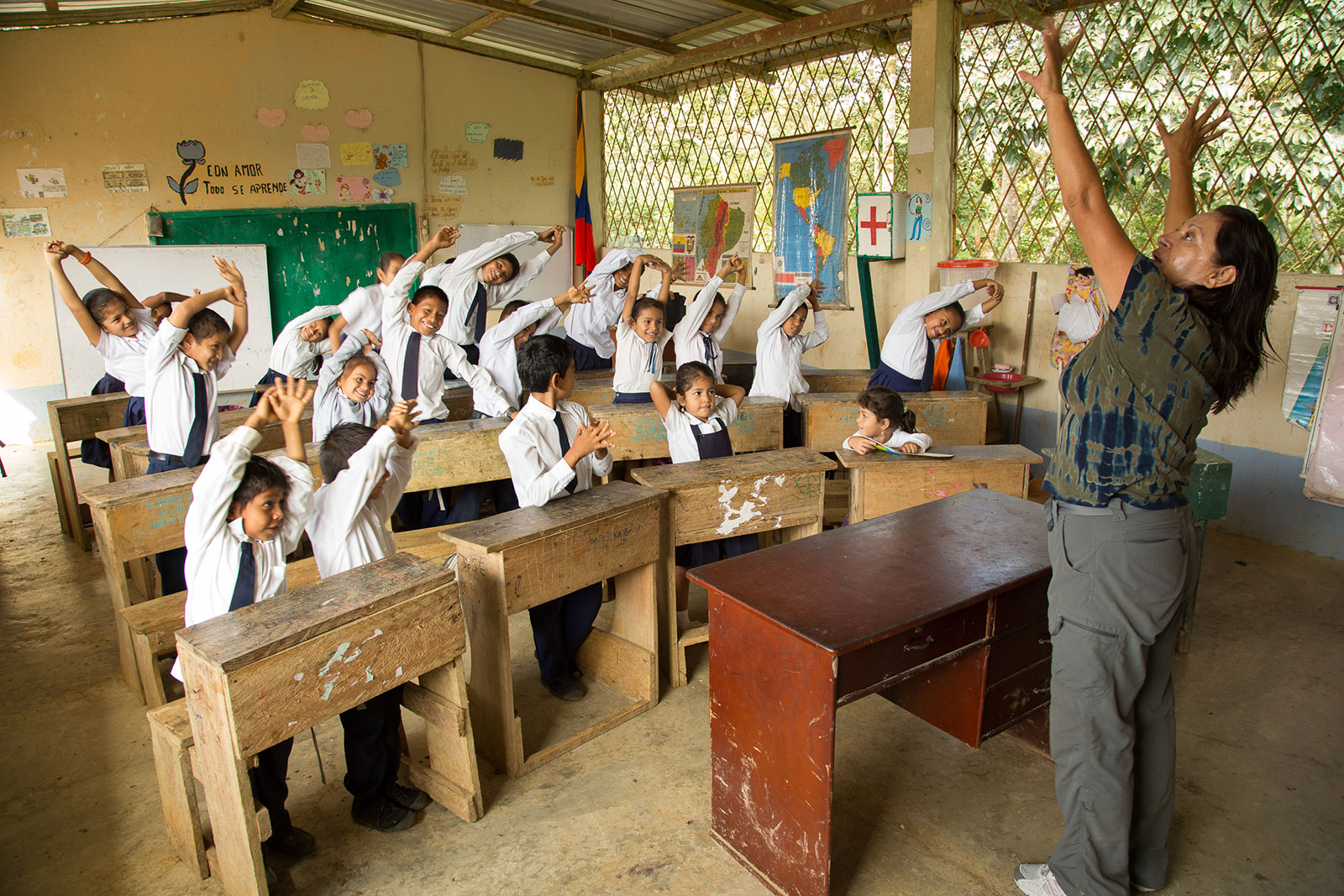 A woman instructs a group of young students to raise their hands in the air