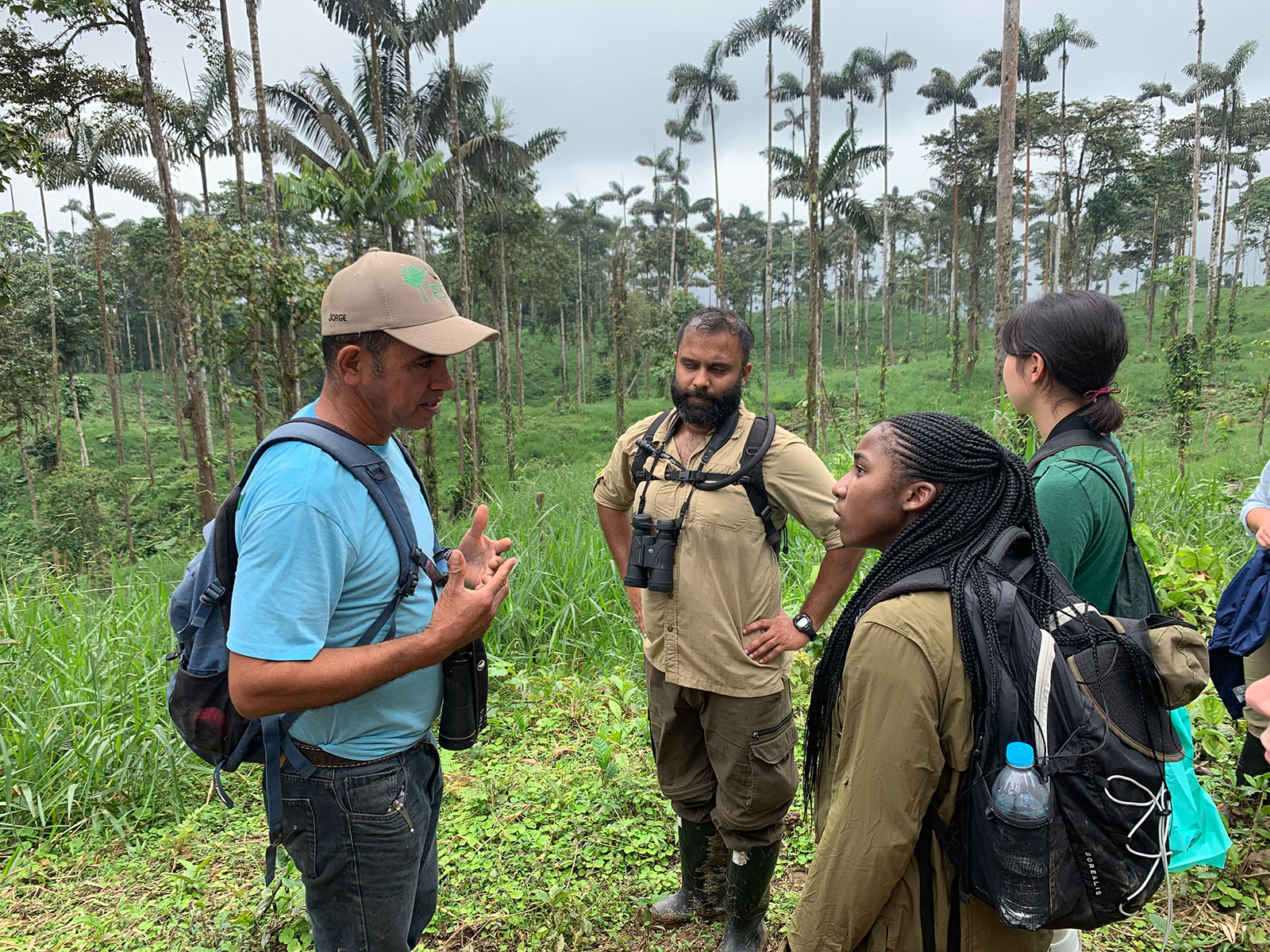An instructor teaches a small group on a field course in the forest