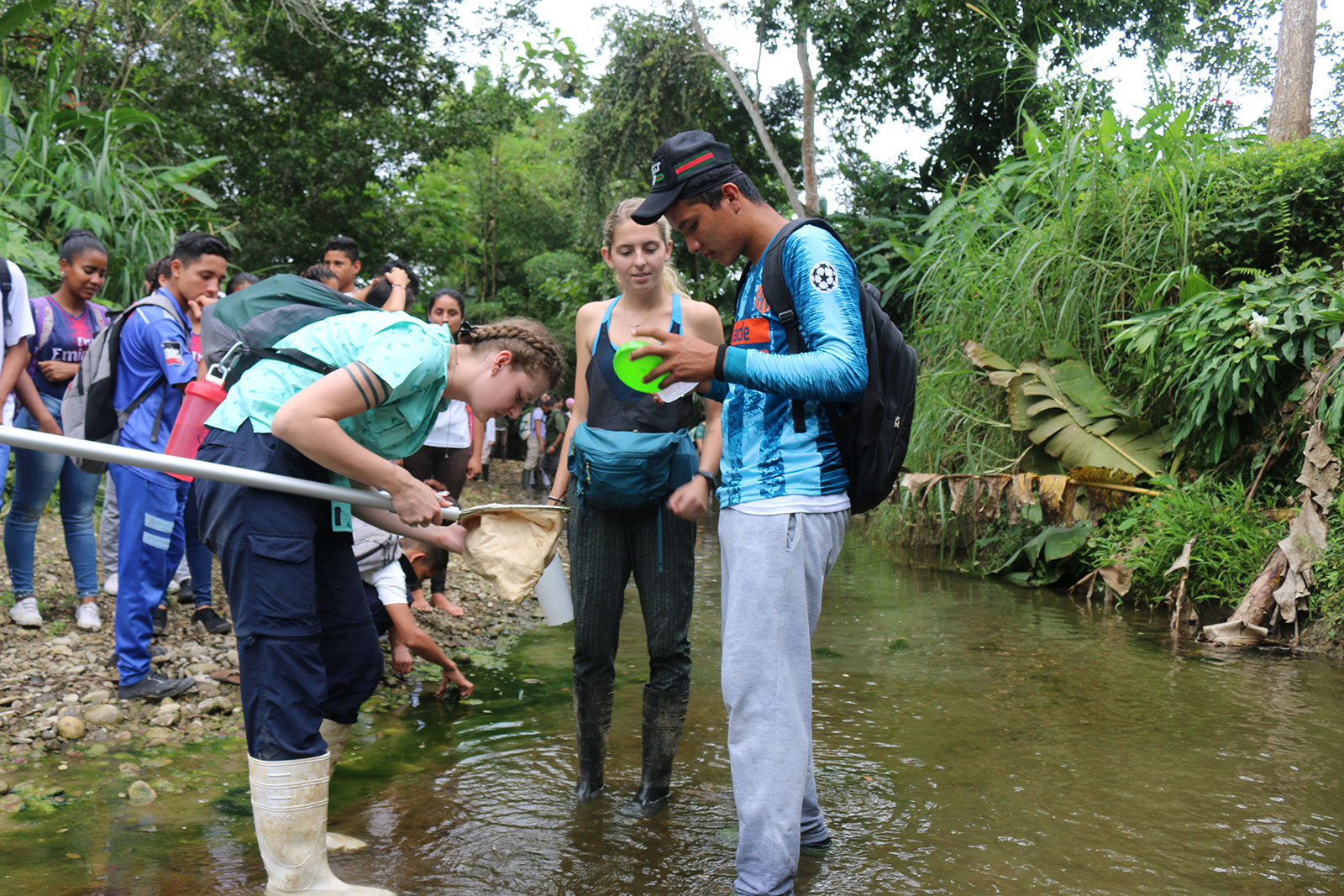 Teenagers examine the contents of a stream