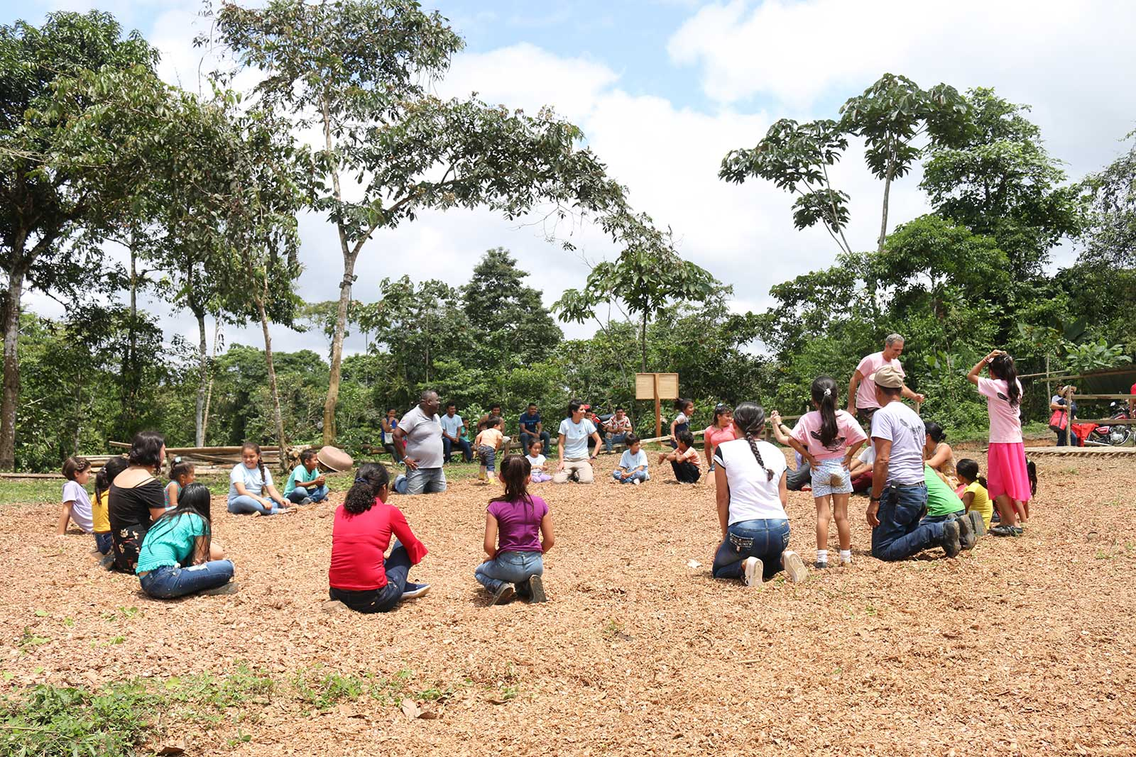 A group of school kids sit in a circle on the ground