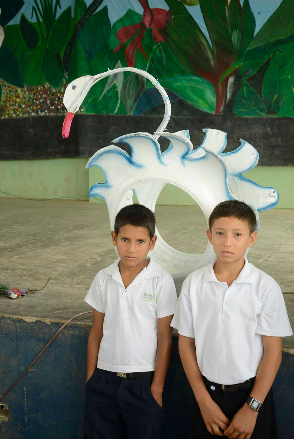 Two schoolboys pose for a picture in front of a statue of a swan