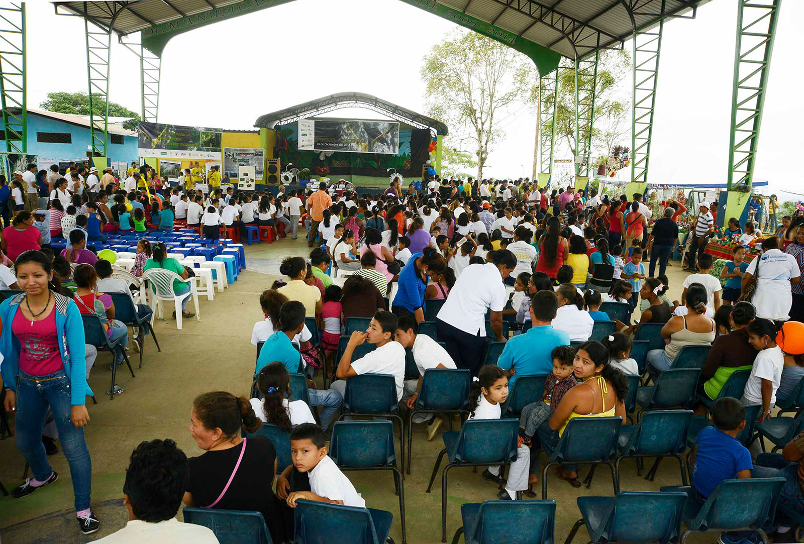The stage and crowd at a large gathering under a pavillion
