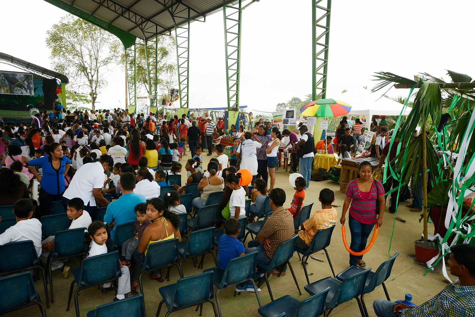People gather for a seated event under a large pavillion