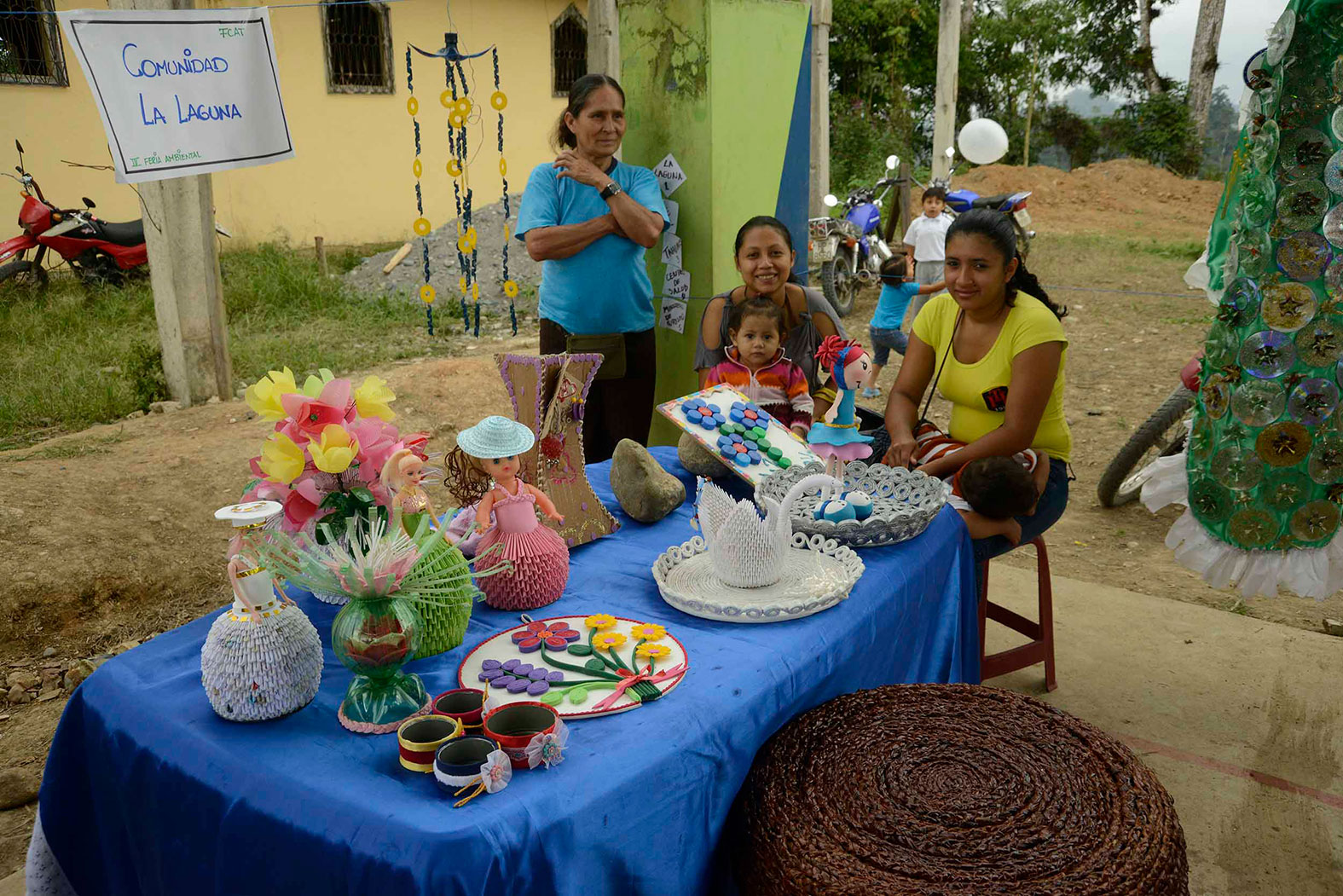 A group of women sit beside a table of handmade crafts