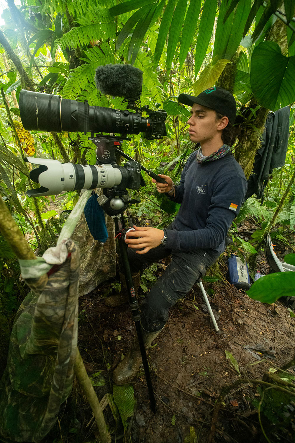 A photographer setting up his cameras in the forest