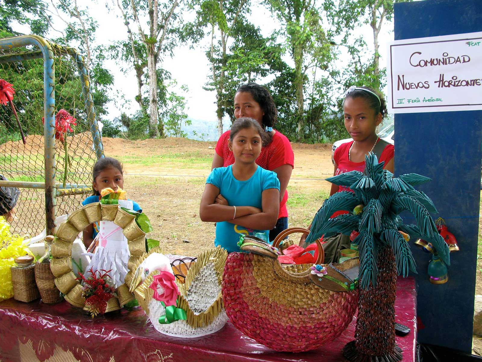 A woman and three girls selling a variety of woven items