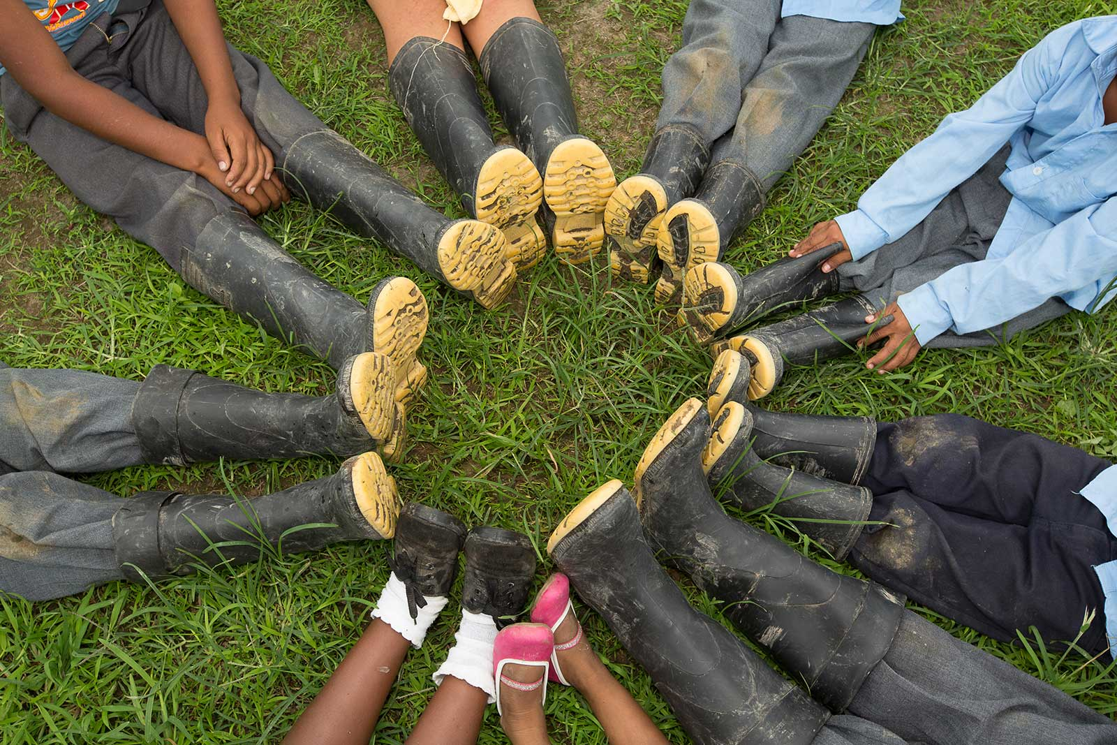 Students wearing work boots sit in a circle with their feet together in the center